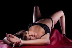 sexy young woman lying on silk sheet - stock photo