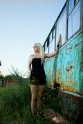 blonde woman standing near abandoned bus - stock photo