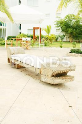 Stock photo of home exterior patio with handcraft wooden sofa with an aligator appearance.