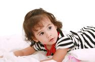 Baby girl lying on the bed with swimsuit with space for advertising Stock Photos