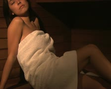 A woman relaxing in a sauna - stock footage