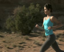 Woman running outdoors with red rock Stock Footage