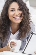 Woman smiling drinking tea or coffee using tablet computer Stock Photos