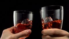 Two glasses of whiskey toasting, Slow Motion Stock Footage