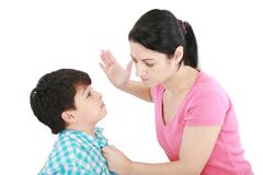 scared 8 year old boy being abused or abducted by adult female. - stock photo