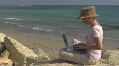 Beautiful woman working on laptop on the beach, coastline businesswoman, holiday Stock Footage