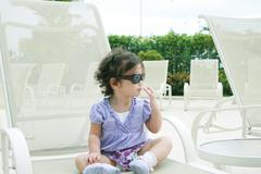 adorable young baby girl wearing sunglasses in flirting position - stock illustration
