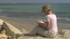 Beautiful woman reading and drinking white wine on the beach, holiday, learning Stock Footage