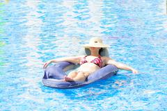 Woman resting and tanning in the pool Stock Photos