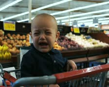 Baby crying in shopping cart Stock Footage