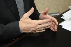Gesticulating hands of a businessman giving an interview Stock Photos