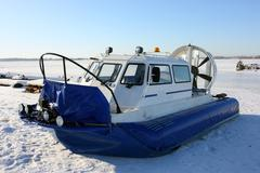 Hovercraft on the bank of a frozen river against a blue sky - stock photo