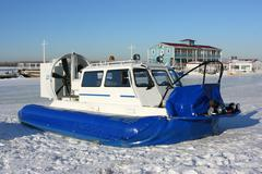 Hovercraft on the bank of a frozen river against a blue sky Stock Photos