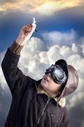 boy as an old style pilot holding a toy airplane, heaven background - stock photo