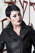 Sexy brunette young woman in a leather jacket over urban background Stock Photos