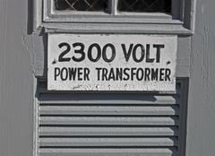 power transformator 2300 volt as text on vintage wooden signboard, energy - stock photo
