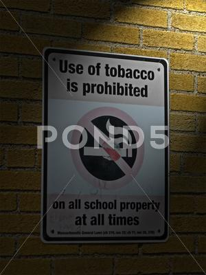 Stock photo of use of tabacco prohibited in all schools as message on sigbboard on brick wal
