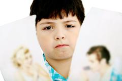 Upset boy standing in front pcture of parents with problems against white bac Stock Photos