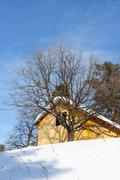 Wooden cottage against a blue sky in the winter Stock Photos