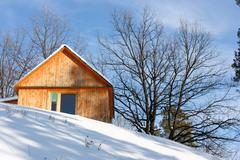 Wooden cottage against a blue sky in the winter - stock photo