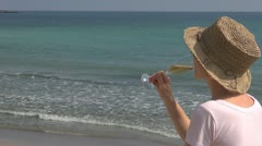Beautiful woman drinking white wine on the beach, sea, wave, glass, summer Stock Footage