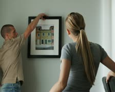 Couple deciding which picture to hang on the wall Stock Footage