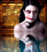 Woman vampire with blood in his mouth. gothic image halloween over gold backg Stock Photos