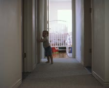 Wide shot of a baby boy carefully working his way down a hallway as he is just Stock Footage