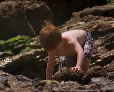 Medium shot of a little redheaded boy as he crwals up a rock while playing and Stock Footage
