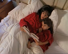 Mother and daughter in red pygamas laying in white bed reading together Stock Footage
