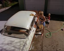 A caucasian boy sprays his mom with a hose who then turns the hose on him while Stock Footage