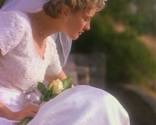 Medium shot portrait of a young blonde bride in her wedding dress and veil as Stock Footage