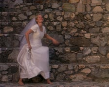 Wide shot as a young blonde bride playfully dances in her white wedding dress Stock Footage