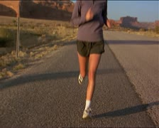 Wide tracking shot of a young blonde female jogger as she runs down the side of Stock Footage