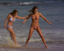 Wide shot of two attractive female friends in bikinis run and frolic along the Stock Footage