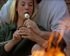 Medium two shot os a young caucasian couple as they sit at a camp fire and Stock Footage