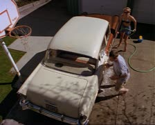 wide high angle shot as a young couple washes their classic car and they begin a - stock footage