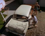 Stock Video Footage of wide high angle shot as a young couple washes their classic car and they begin a