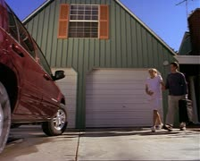 Wide shot as a young expectant couple walks out of their house and into their Stock Footage