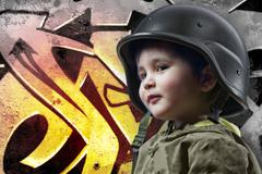 baby playing war with military helmet against graffiti background with intens - stock photo