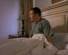 medium tracking shot as a caucasian woman brings her husband breakfast in bed - stock footage