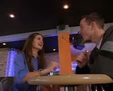 Medium tracking two shot as a young caucasian couple talk while being served by Stock Footage