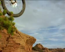 A male mountain biker jumps over the camera with his bike in the southwest Stock Footage