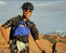 A man on mountain bike and in biking gear looks toward camera and laughs Stock Footage