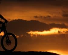 Three mountain bikers ride across sunset Stock Footage