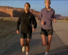 Two women running on road in the southwest outdoors Stock Footage