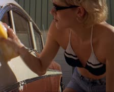 Blonde caucasian woman wearing sunglasses, bikini top and cut-off shorts washes Stock Footage