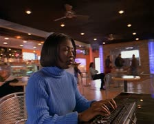 An african-american woman sits at computer in cafe and types while caucasian Stock Footage