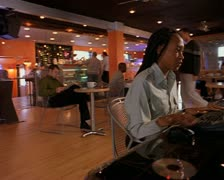 An african-american woman sits at a computer in a cafe and types Stock Footage