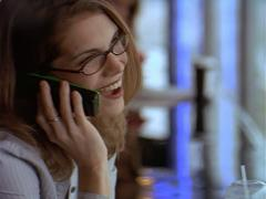 Caucasian woman wearing black glasses and gray sweater talks on her cell phone Stock Footage